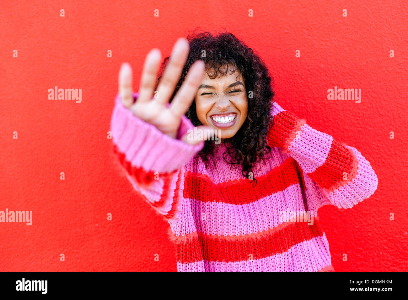 Portrait of laughing young woman in front of red wall Photo Stock
