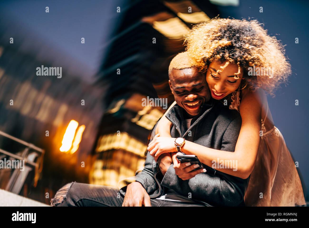 Jeune couple looking at smartphone par nuit Banque D'Images