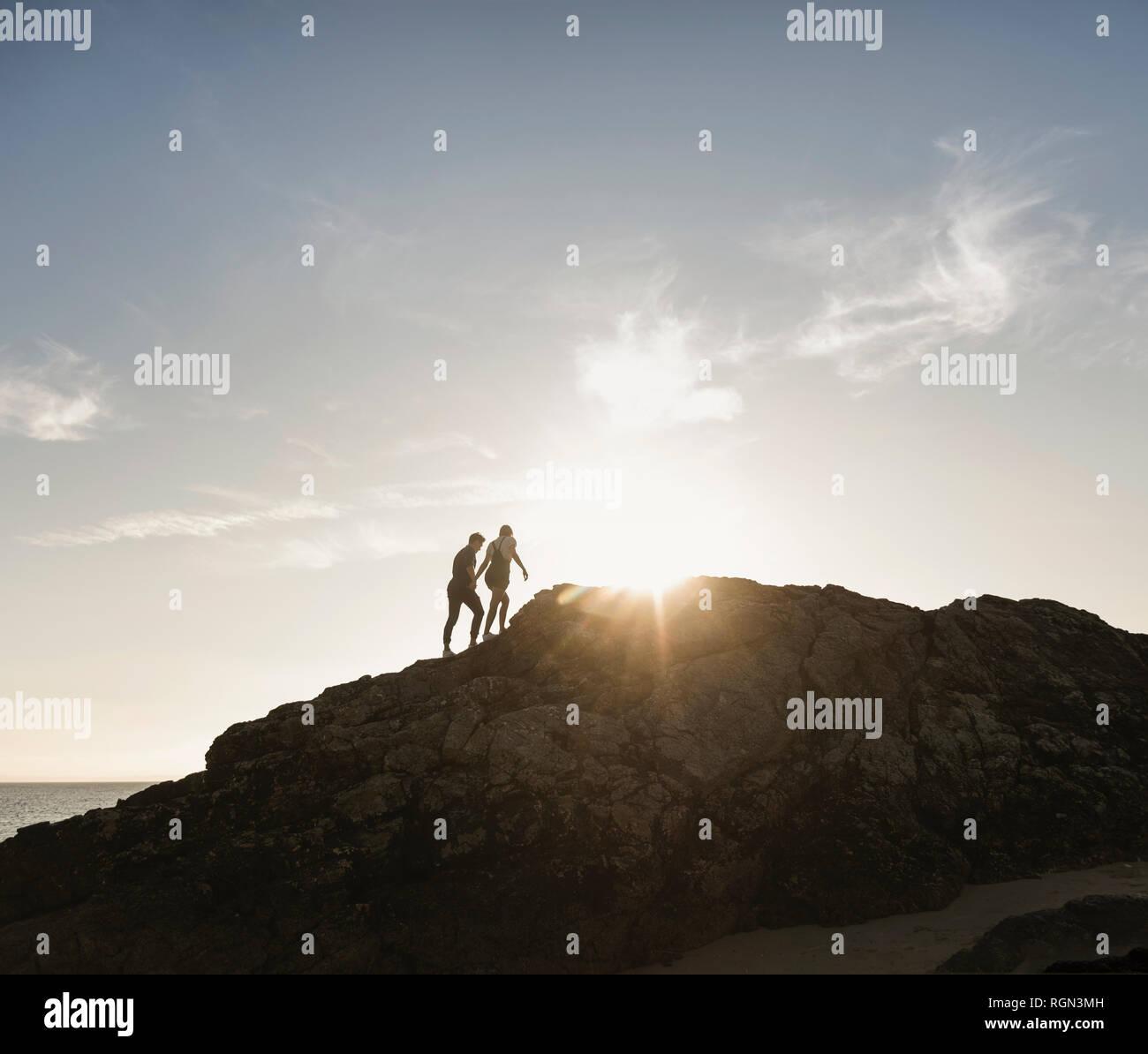 France, Bretagne, jeune couple d'escalade sur un rocher sur la plage au coucher du soleil Banque D'Images