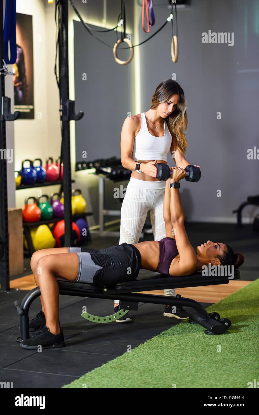 Personal trainer assisting client avec la formation de poids, soulever des haltères, couché sur banc Photo Stock