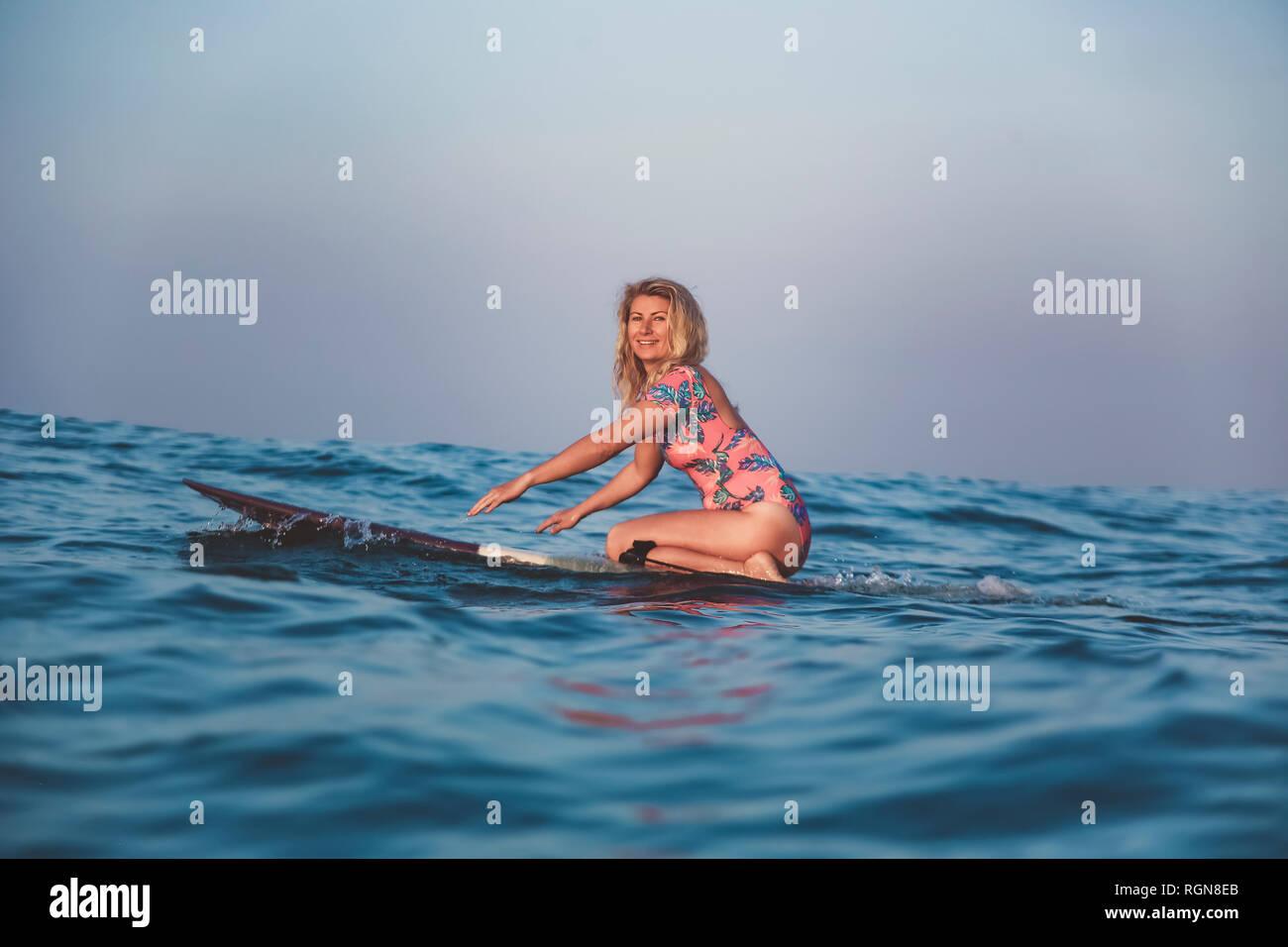 L'INDONÉSIE, Bali, pregnant woman sitting on surfboard Banque D'Images