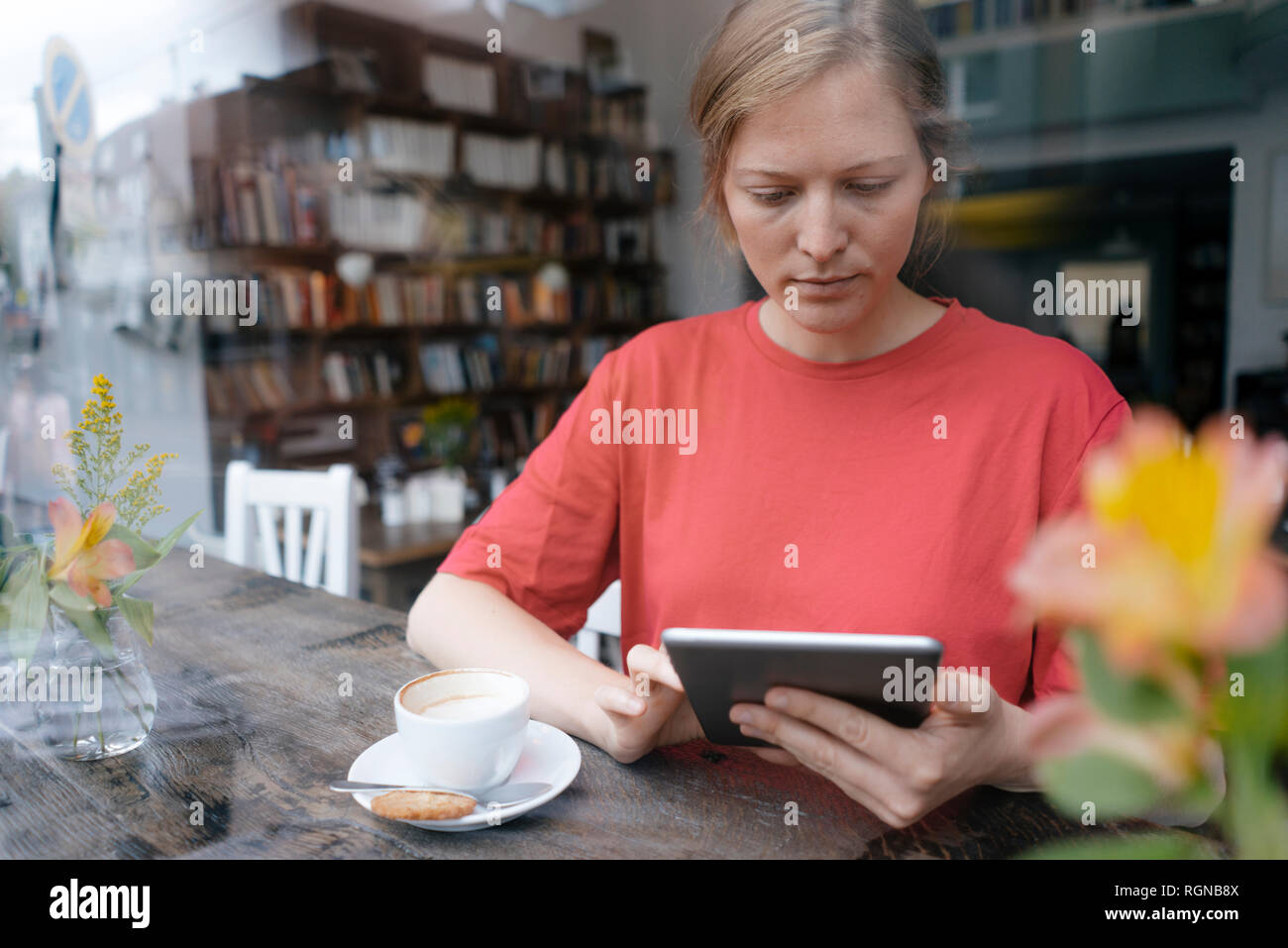 Jeune femme à l'aide de comprimé à la fenêtre dans un café Banque D'Images