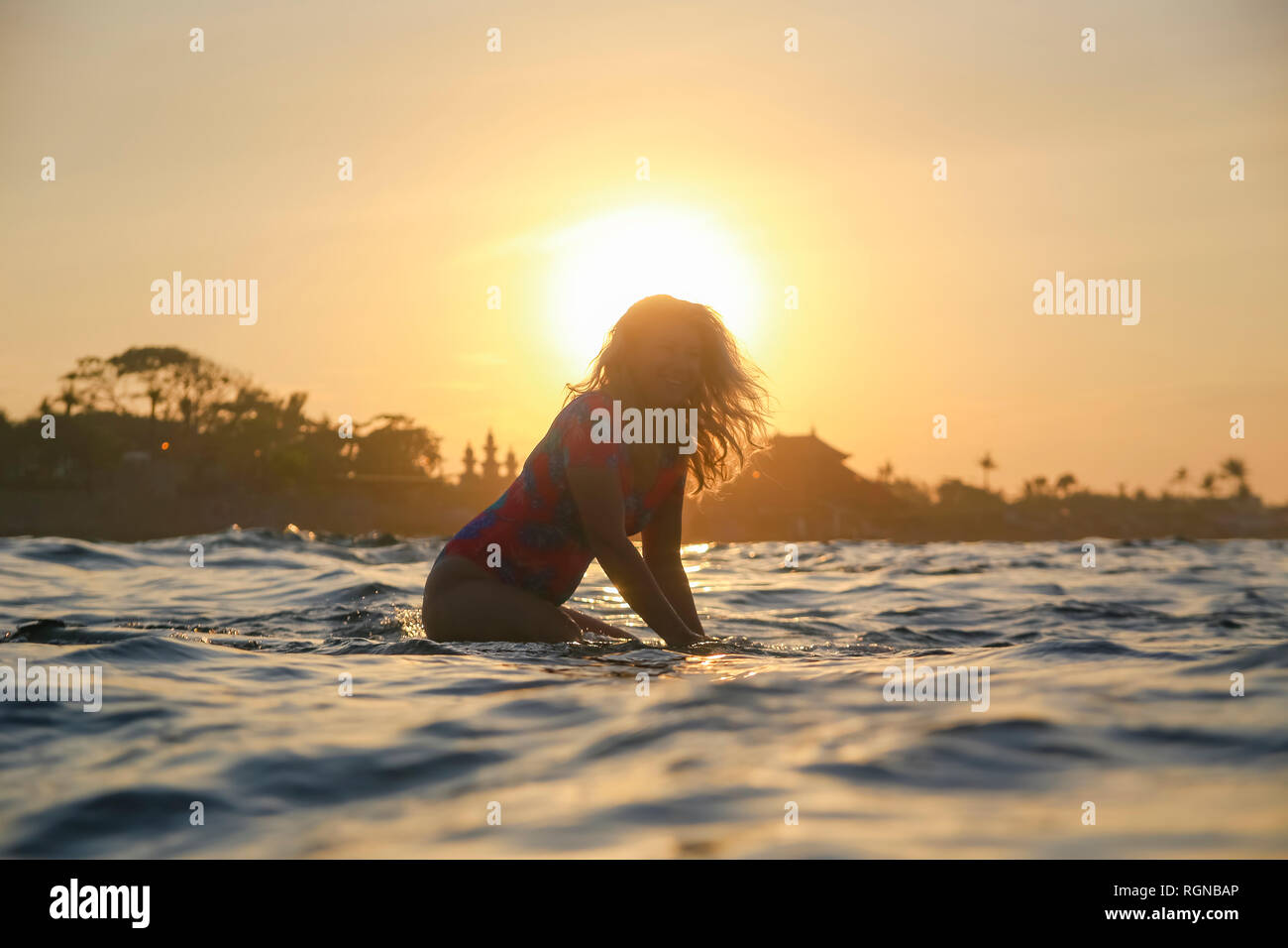 L'INDONÉSIE, Bali, pregnant woman sitting on surfboard au coucher du soleil Banque D'Images