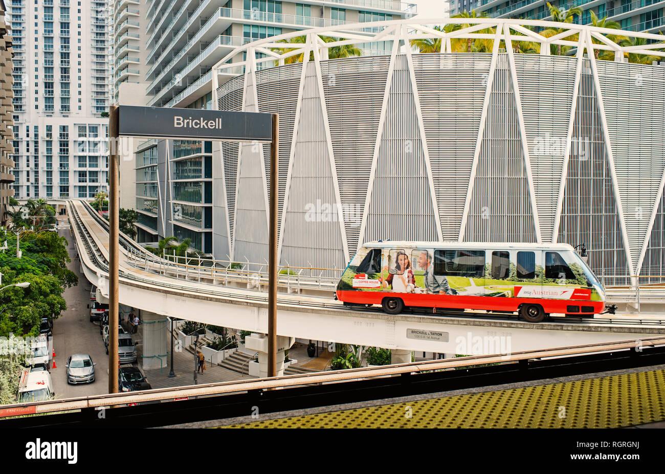 Miami, USA - 30 octobre 2015: train arrive à la station de Brickell avec gratte-ciel sur fond urbain. Metrorail ou metro rail transit system sur la ville. Service de transport métropolitain. Banque D'Images