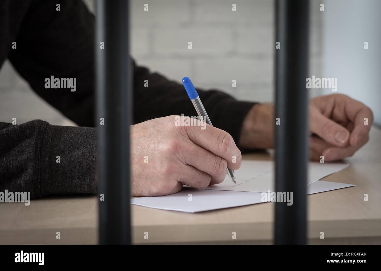 Un prisonnier derrière les barreaux la rédaction d'une lettre Photo Stock