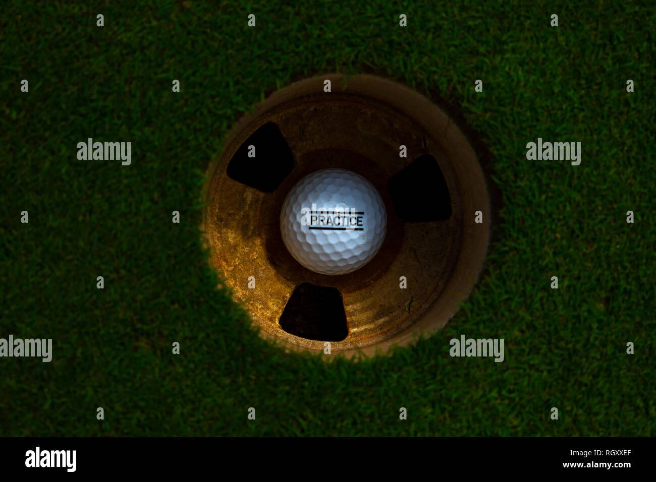 Balle de golf dans le trou sur le putting green avec texte pratique en Suisse. Banque D'Images