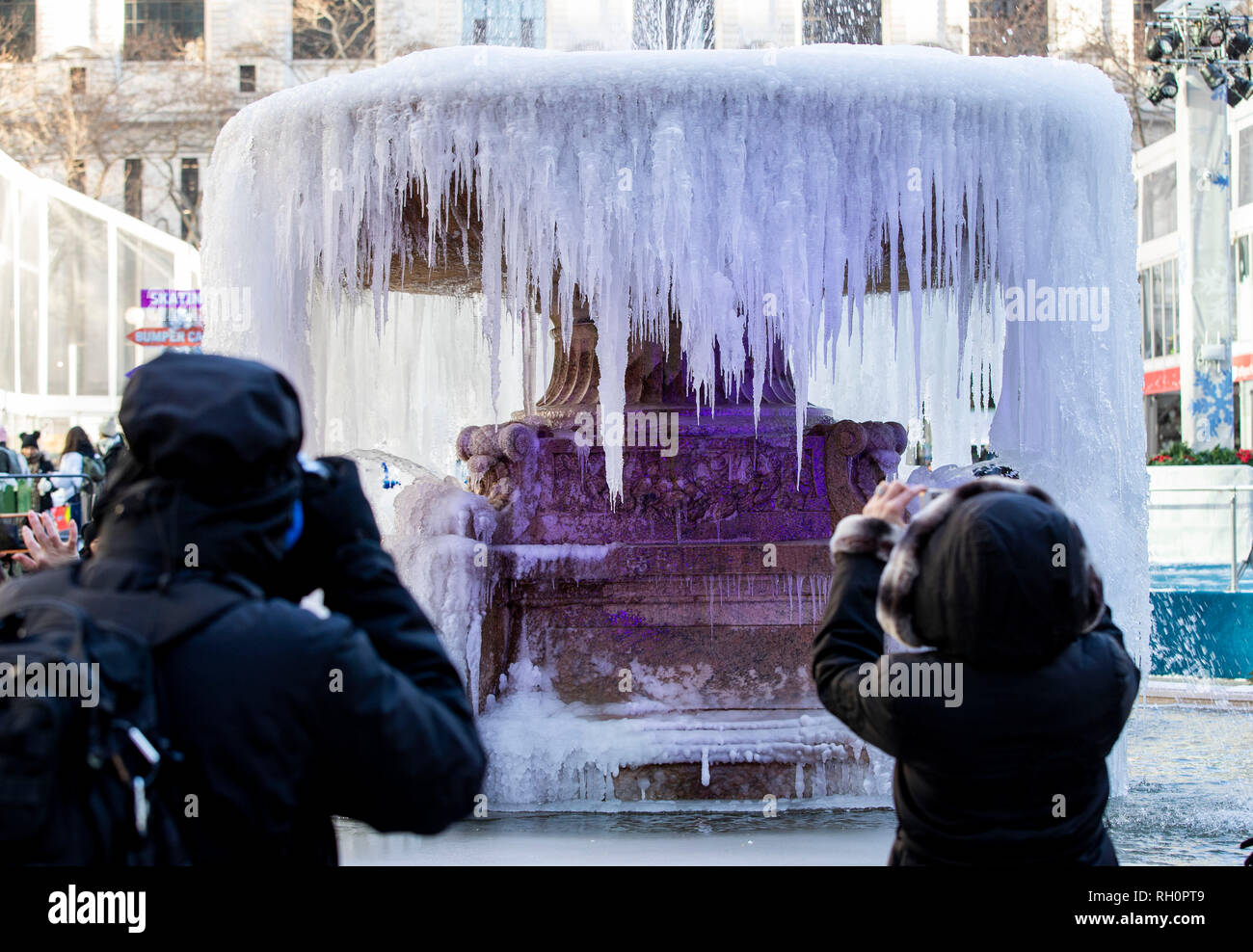 New York, USA. Jan 31, 2019. Les gens de prendre des photos en face d'une fontaine en Bryant Park à New York, États-Unis, le 31 janvier 2019. Le temps de gel causé par le vortex polaire dans le midwest des États-Unis s'est élargie pour New York depuis mercredi avec neige et de fortes rafales de vent, des températures à l'envoi de 10 degrés Fahrenheit, ou au-dessous de -12 degrés Celsius. Credit: Wang Ying/Xinhua/Alamy Live News Photo Stock