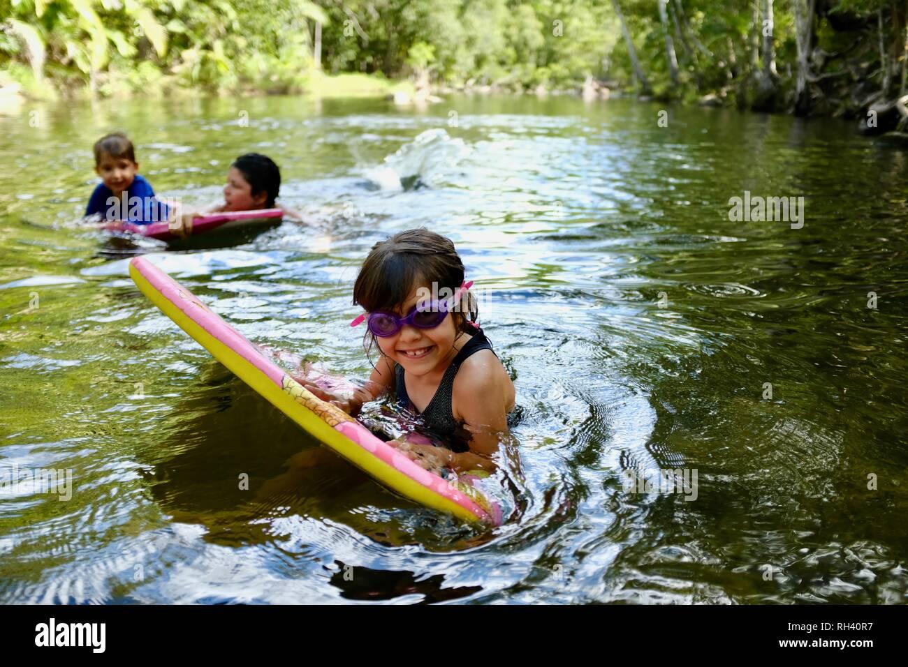 Jeune fille paddles sur une planche de surf avec la famille en arrière-plan, Finch Hatton, Queensland 4756, Australie Banque D'Images