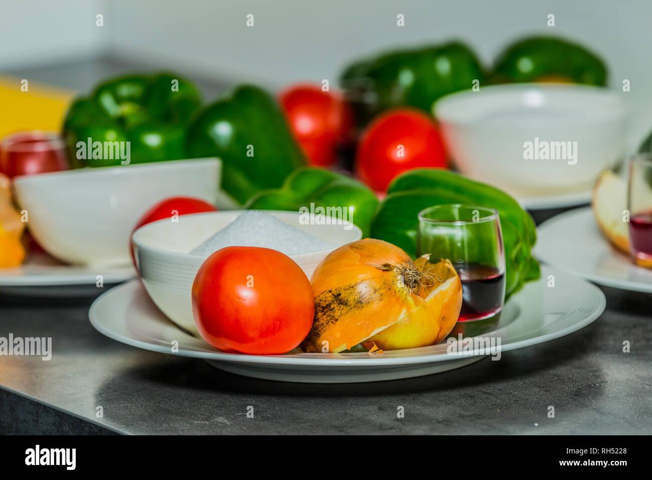 Plaque en céramique blanche avec la tomate, l'oignon, le poivron vert, le sucre dans un bol et le vinaigre dans une tasse en verre sur une table en métal, une combinaison de couleurs et de textures Photo Stock
