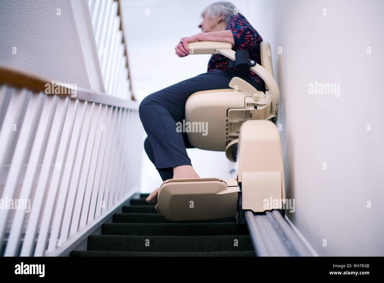 Senior Woman Sitting on monte-escalier à la maison pour aider à la mobilité Photo Stock