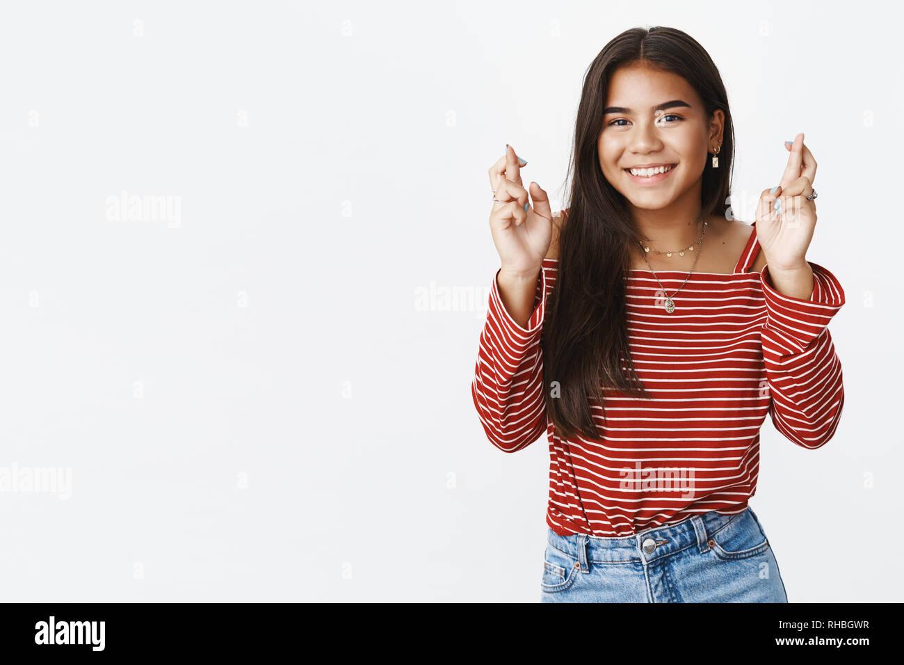 D'espoir et d'optimisme charmante jeune femme pense rêve crossing fingers pour la bonne chance et smiling at camera de décisions positives tiens Photo Stock