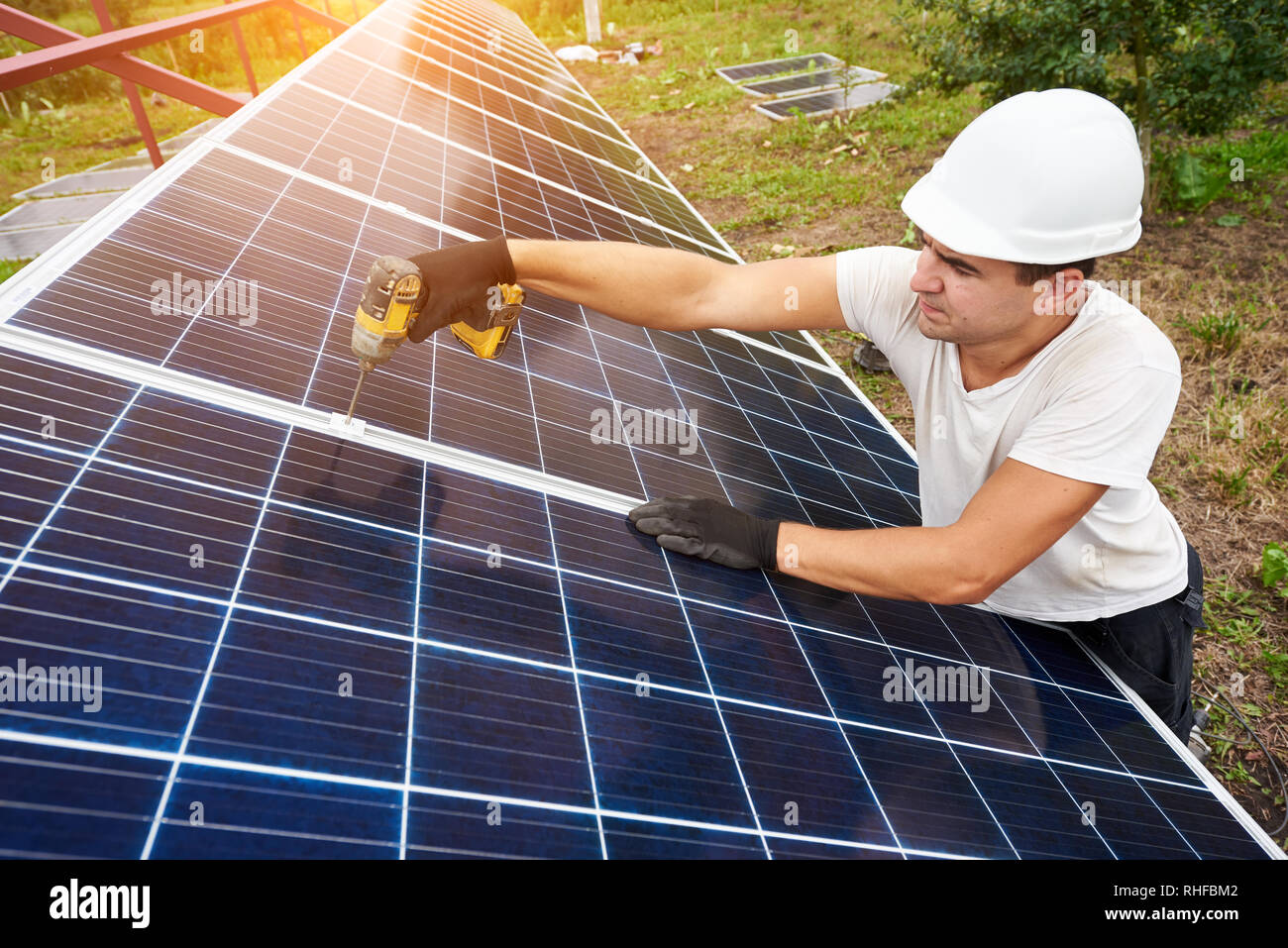 Technicien professionnel travaillant avec tournevis connexion panneau photovoltaïque à l'extérieur de la plate-forme de métal sous ciel bleu clair. L'énergie renouvelable de remplacement écologique vert de concept. Photo Stock
