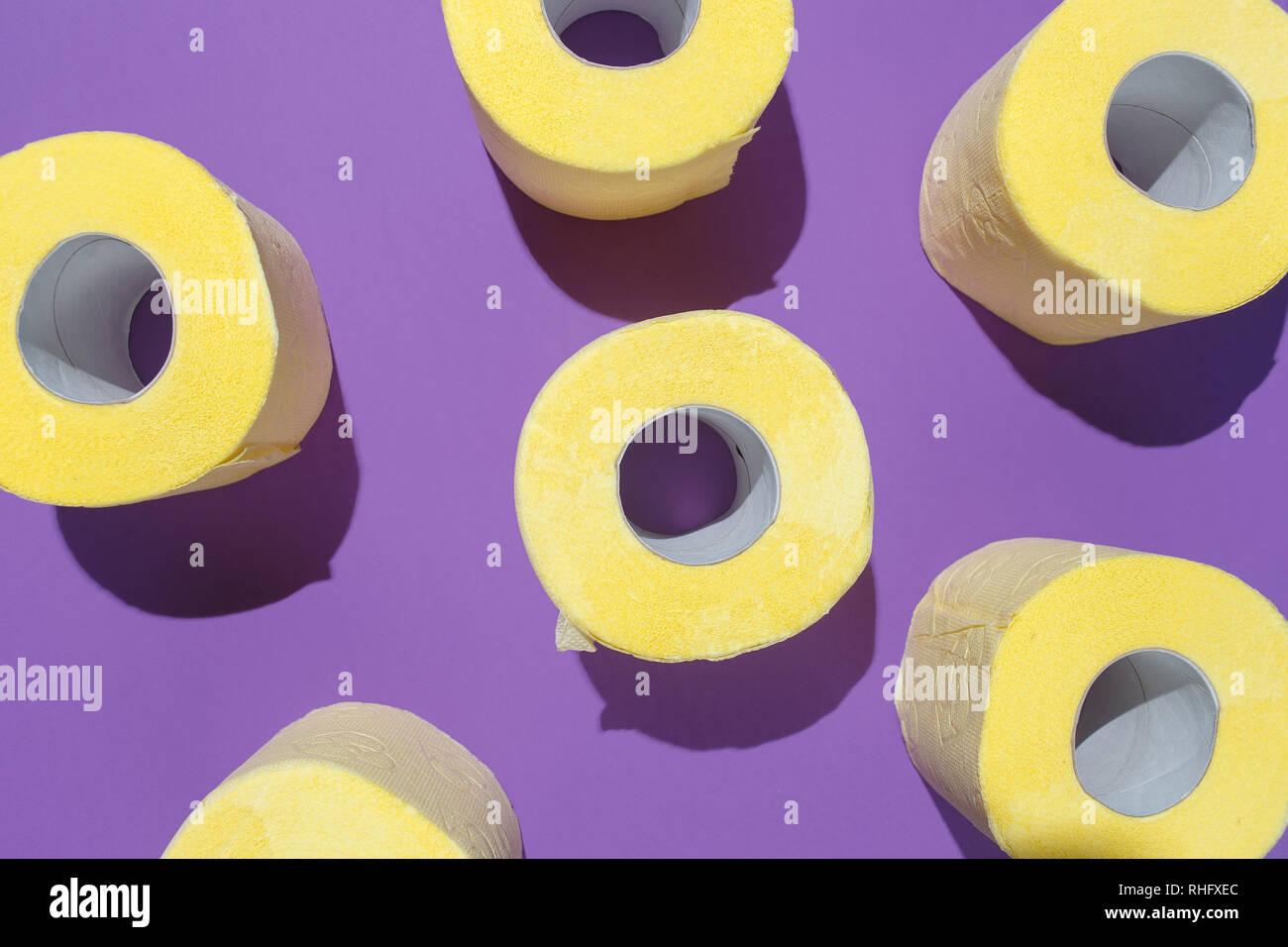 Schéma des rouleaux de papier toilettes jaune vif sur fond violet. Télévision composition, vue d'en haut. Banque D'Images
