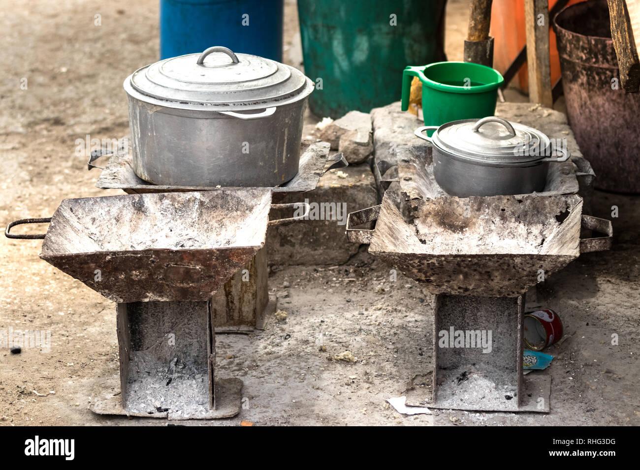 Les poêles du charbon de bois rustique et une batterie de cuisine, casseroles et poêles sur le plancher sur le marché local de Toliara, Madagascar. Photo Stock