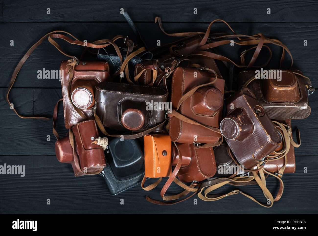 Tas de 35mm en cuir rétro caméras dans le noir, vue de dessus. Collection de vieilles choses et d'antiquités, ventes aux enchères Banque D'Images