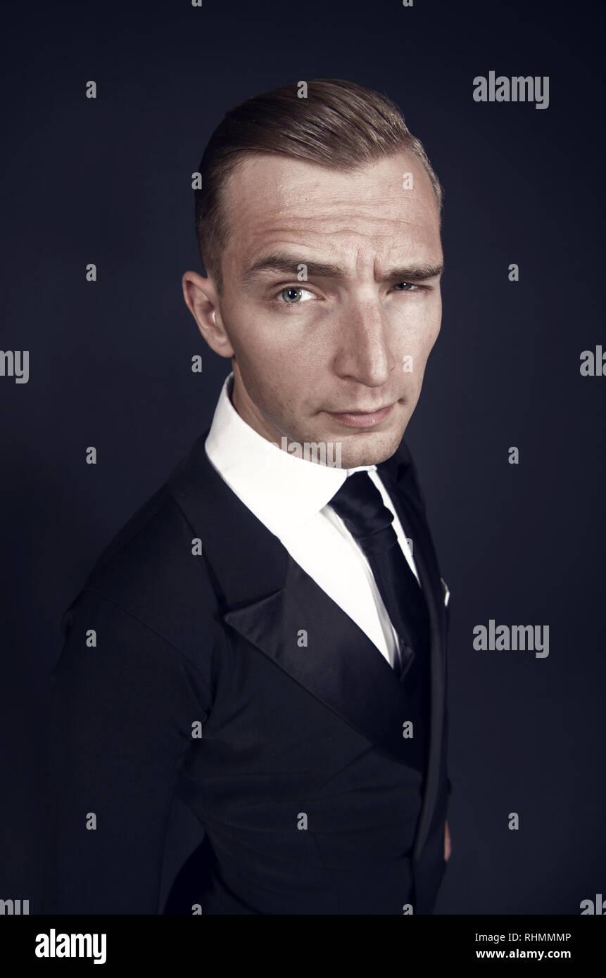 Homme d'affaires en costume noir clin d'œil sur fond sombre. Le flirt, l'intention, l'intérêt, secret, de sympathie, de solidarité, d'entente ou d'intimité concept Photo Stock