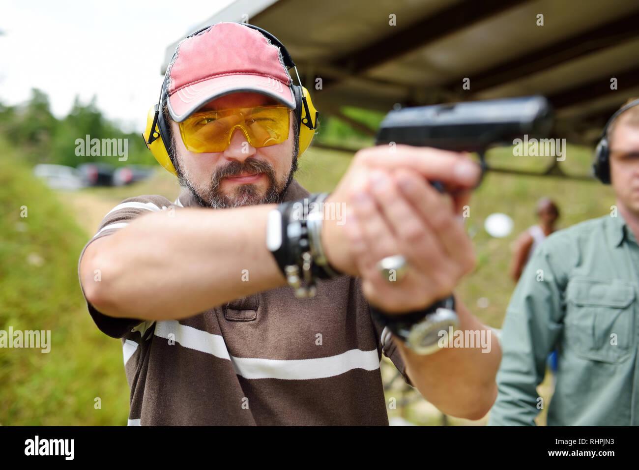 Prise de l'homme sur un stand de tir en plein air. Homme d'armes à feu de tir au but. Des loisirs actifs. Photo Stock