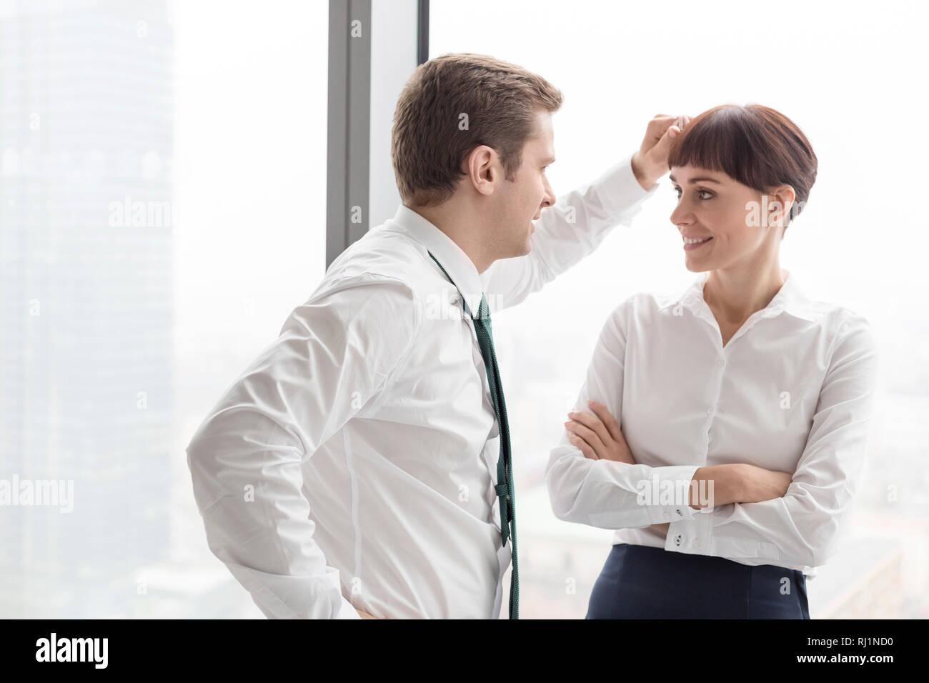 Woman putting businesswoman standing contre fenêtre à modern office Banque D'Images