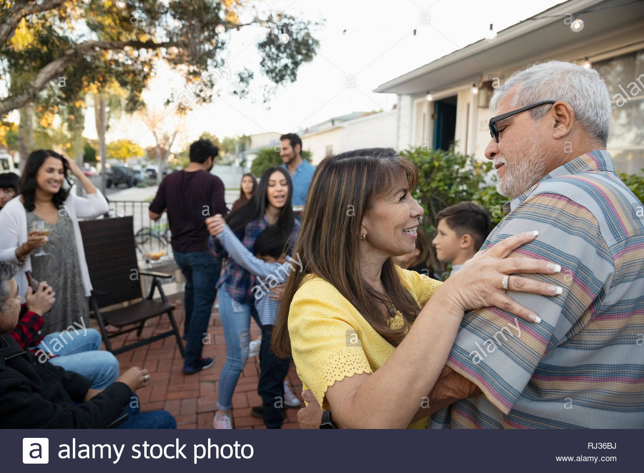 Latinx senior couple dancing on patio Photo Stock