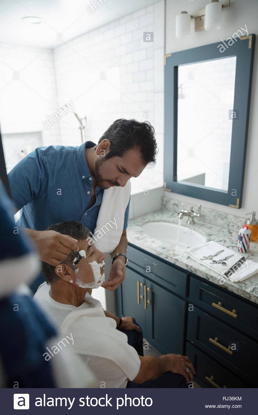 Latinx fils père senior de rasage visage s dans la salle de bains Photo Stock