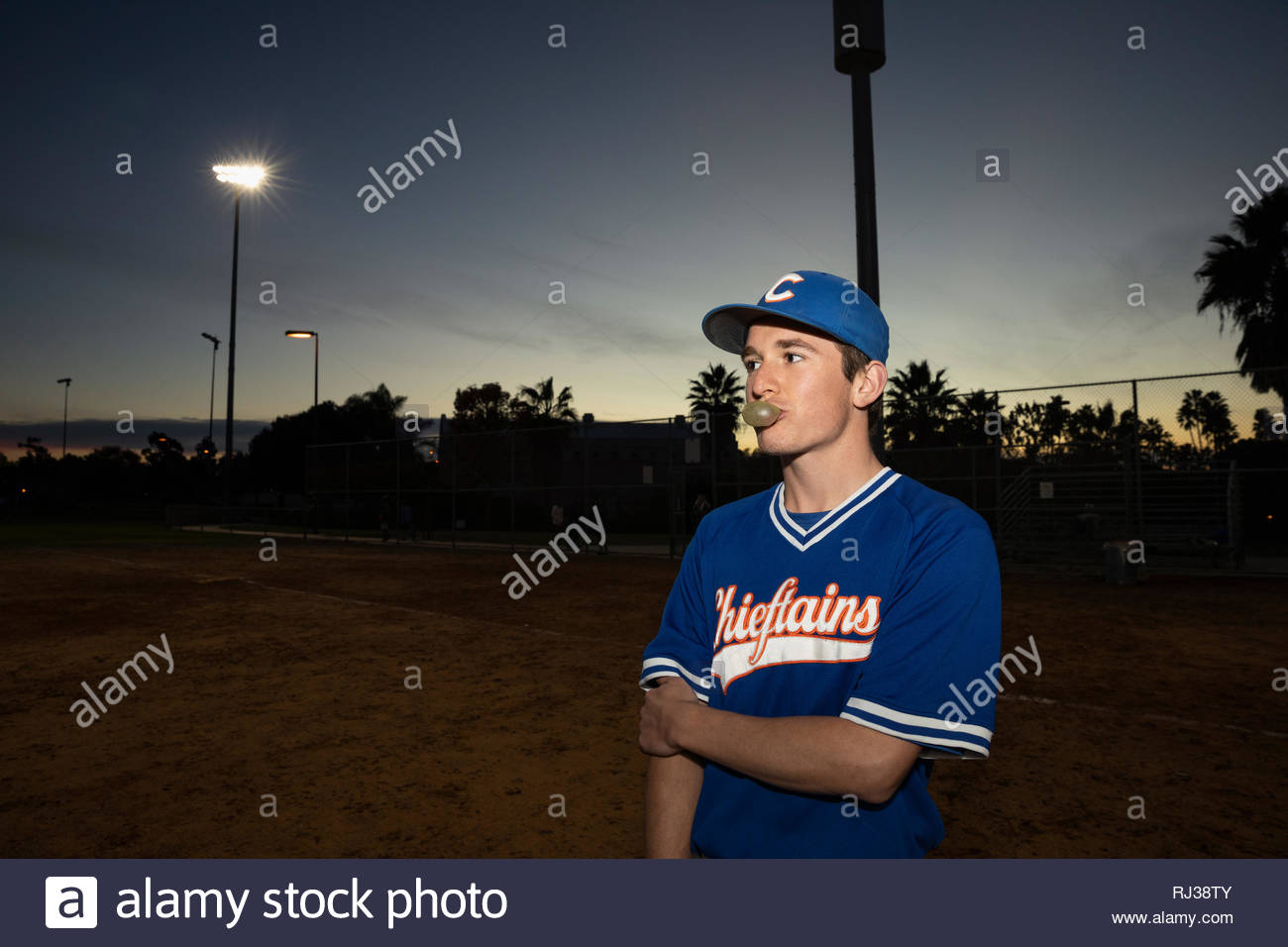Joueur de baseball blowing bubble gum bubble sur terrain de nuit Photo Stock