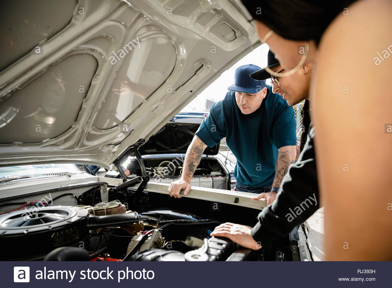 Latinx friends checking out moteur de voiture vintage Photo Stock