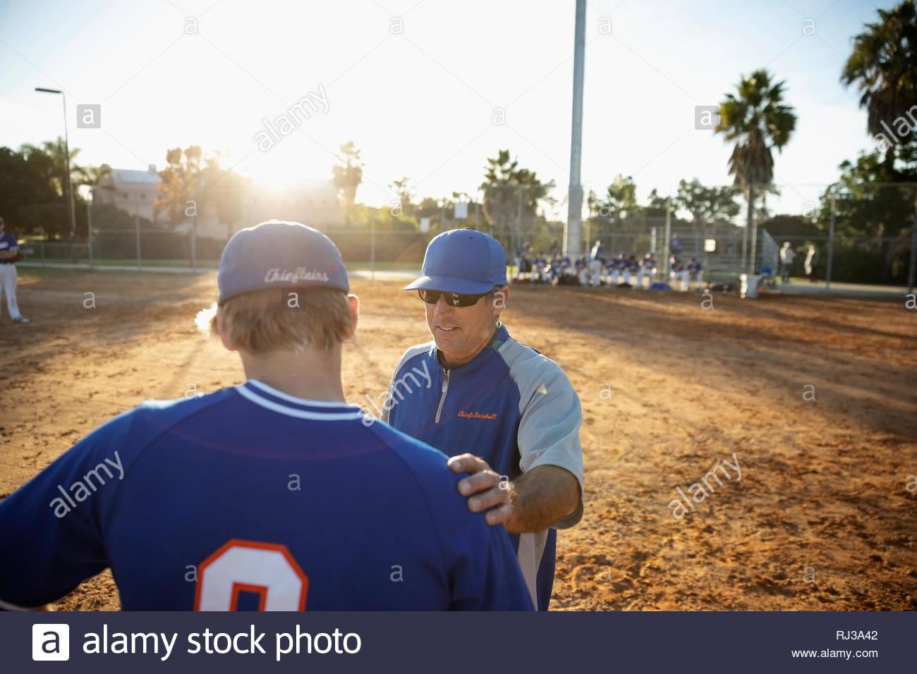 Parler avec l'entraîneur de baseball sur terrain ensoleillé Banque D'Images