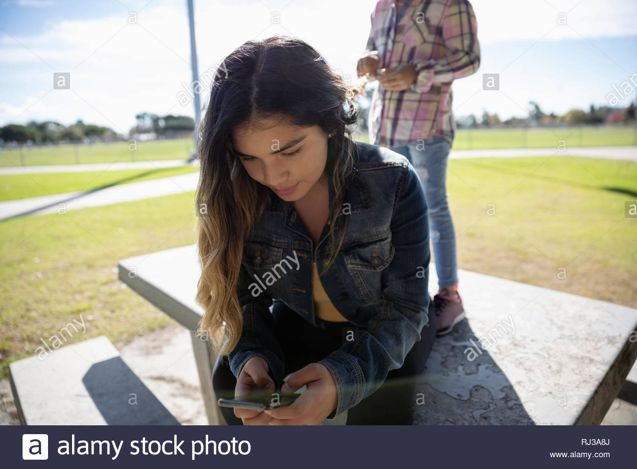 Latinx adolescente texting with smart phone in sunny park Photo Stock