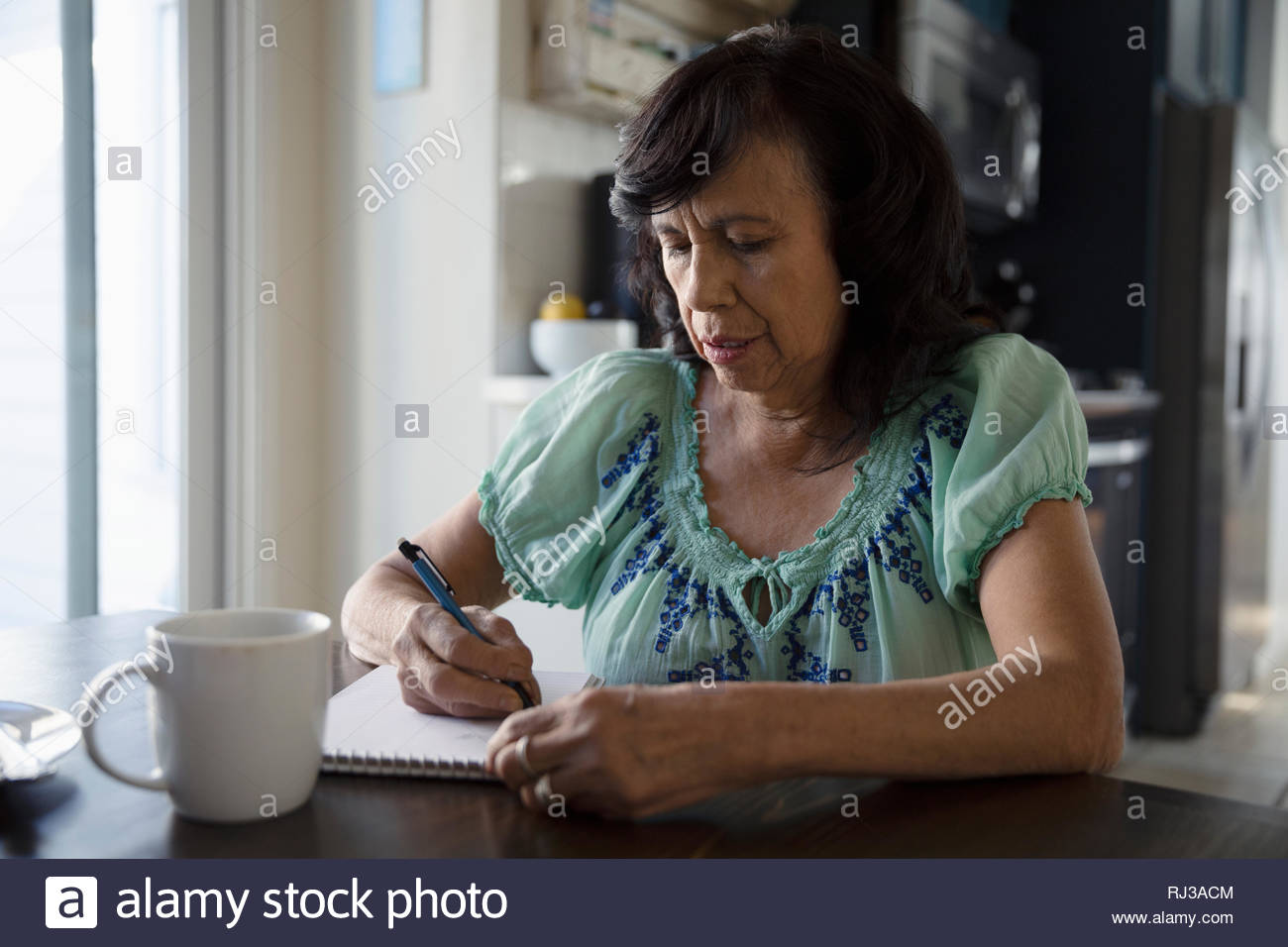 Latinx senior woman writing dans le bloc-notes à la table de cuisine Photo Stock