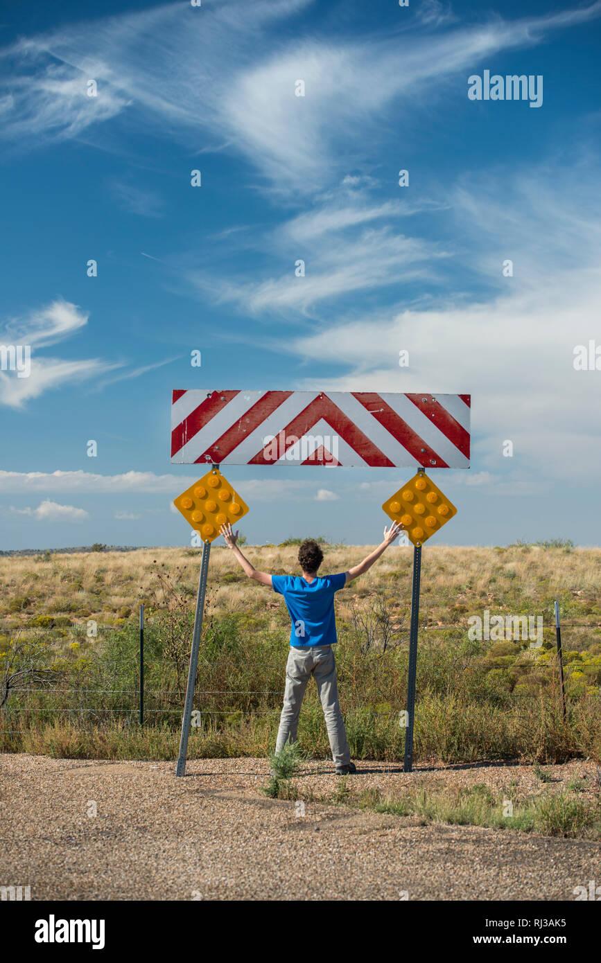 L'homme à bras ouverts sous une autoroute dead end sign. Chaude journée ensoleillée à manches courtes. Photo Stock