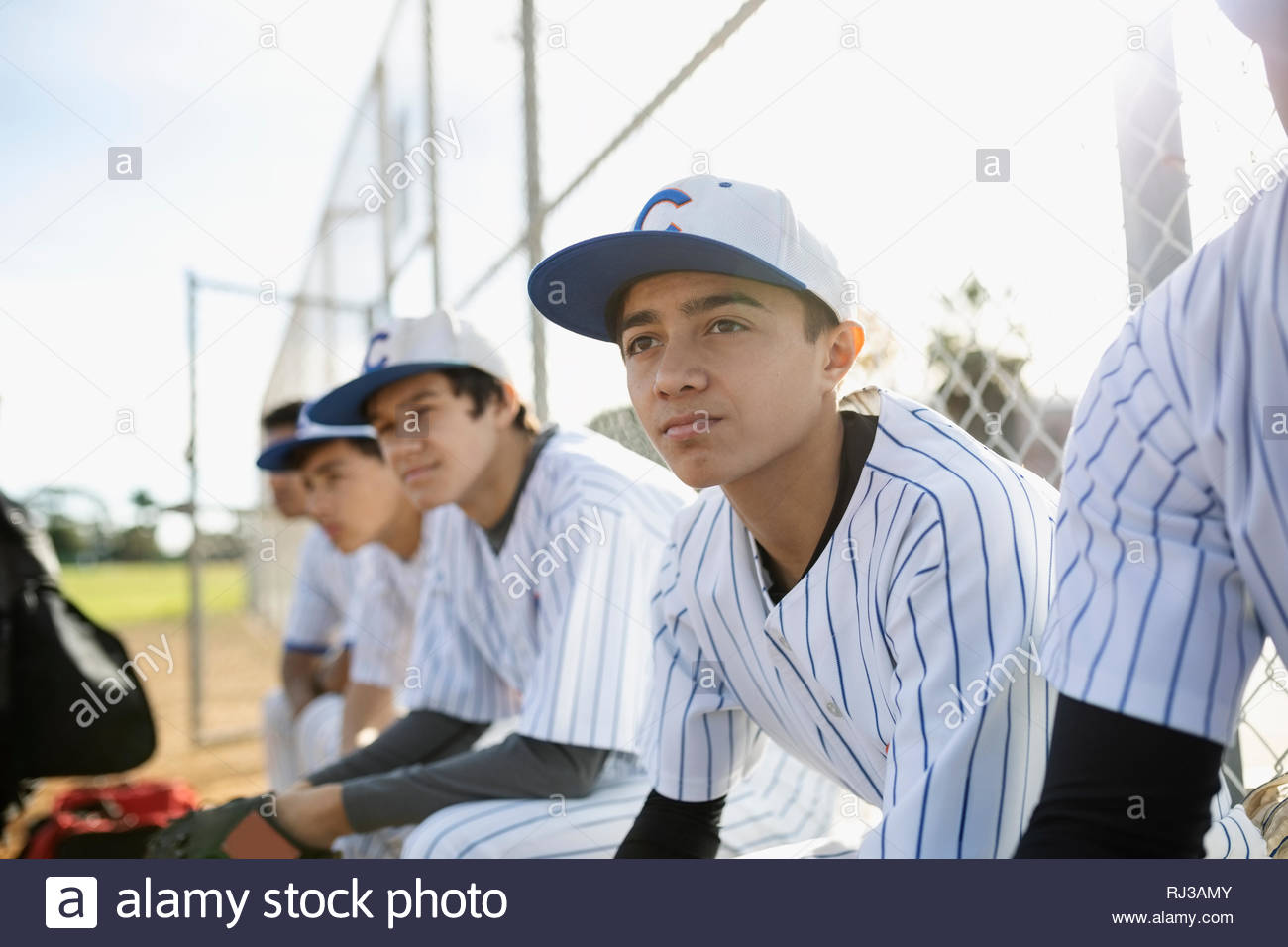Joueur de baseball Latinx en attente sur banc Photo Stock
