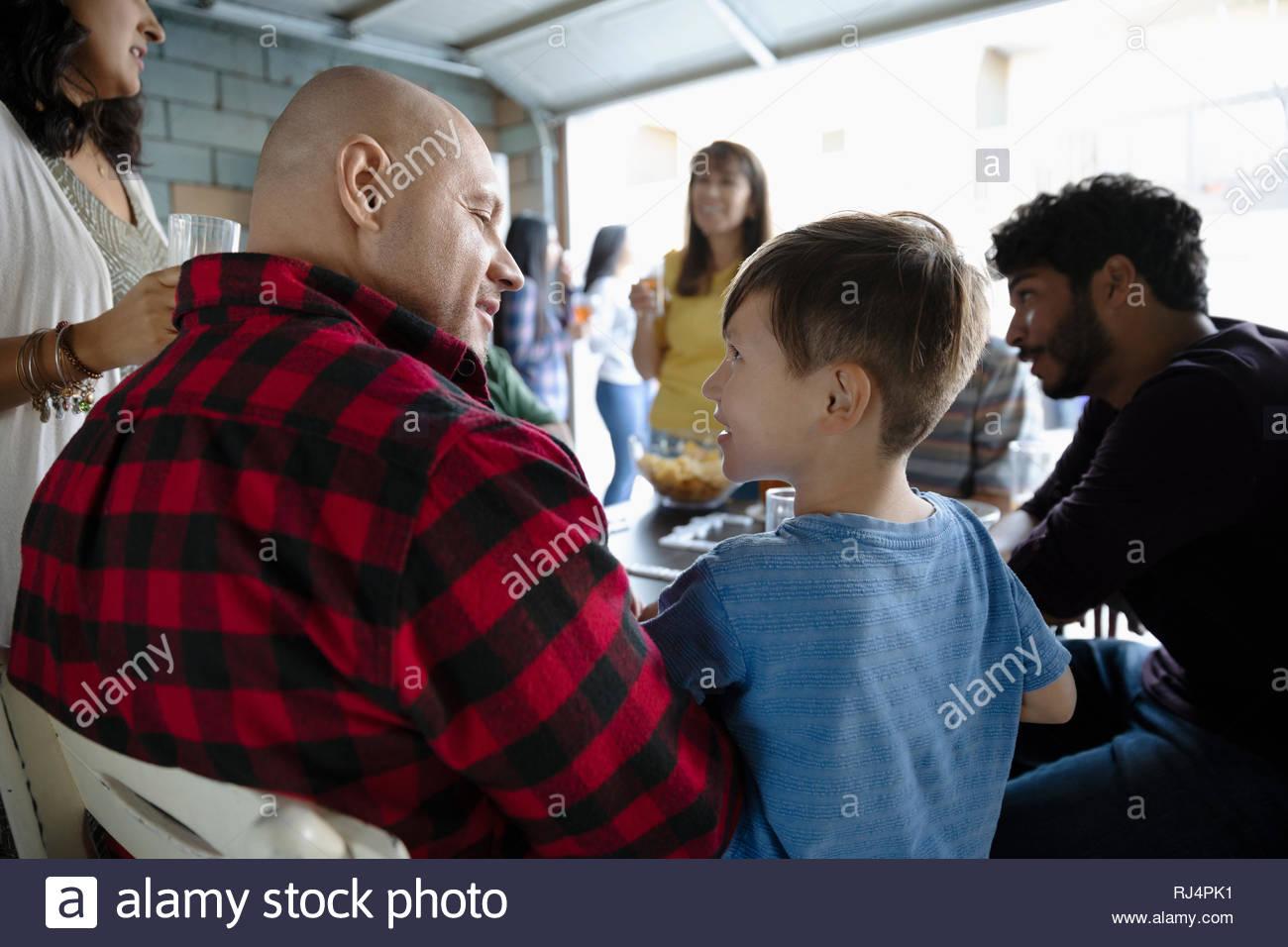 Latinx père et fils jouer aux dominos avec la famille en garage Banque D'Images