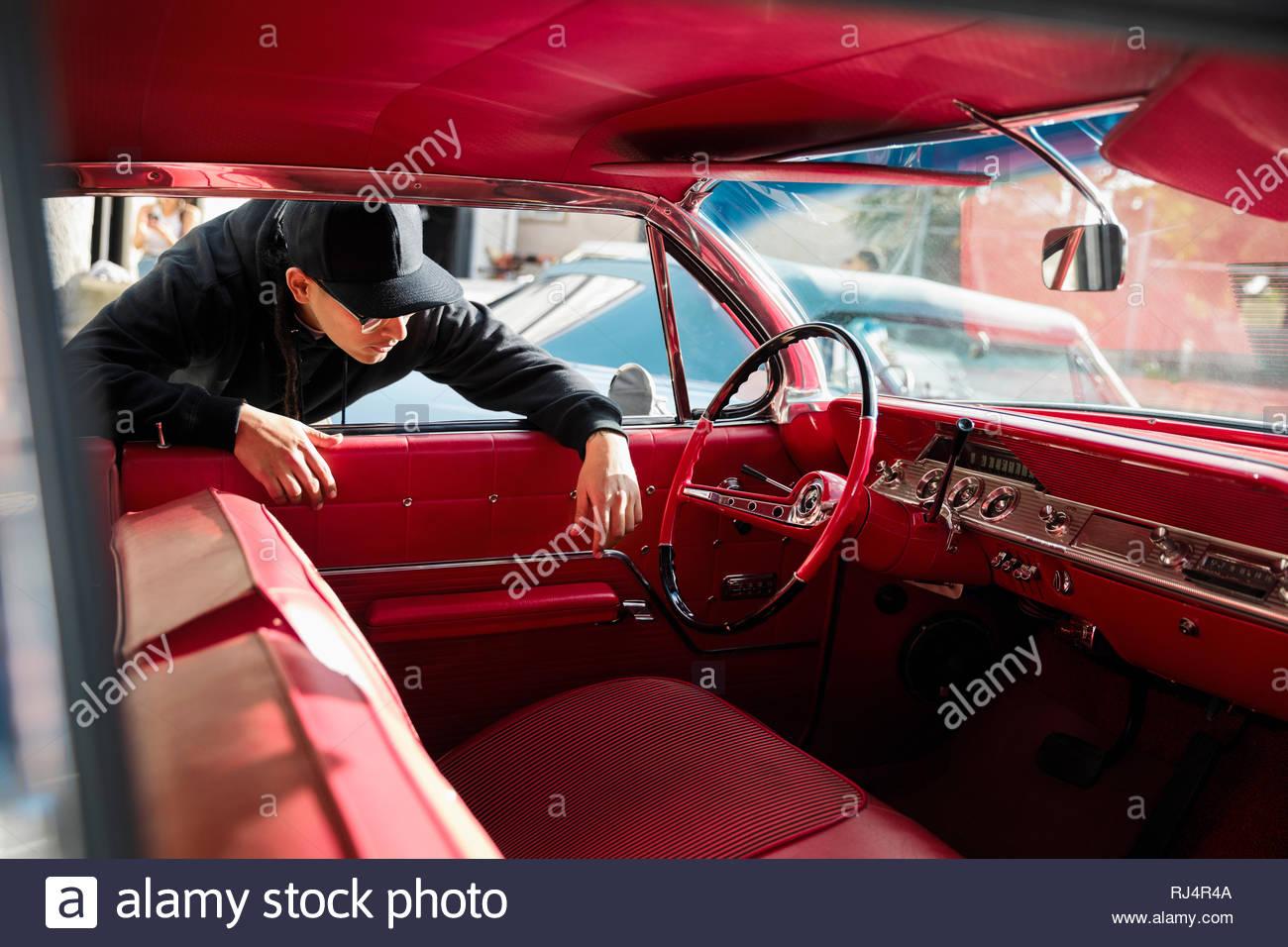 Jeune homme Latinx vérifier l'intérieur en cuir rouge de vintage car Photo Stock