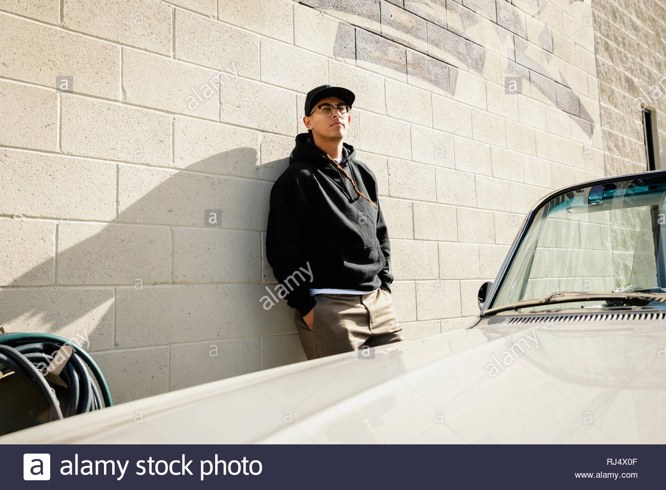 Confiant Latinx young man leaning against wall ensoleillée Photo Stock