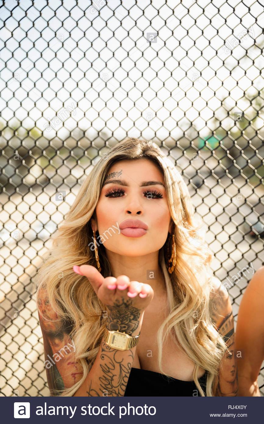 Confiant, cool Latinx Portrait jeune femme avec des tatouages qui souffle dans un baiser Photo Stock