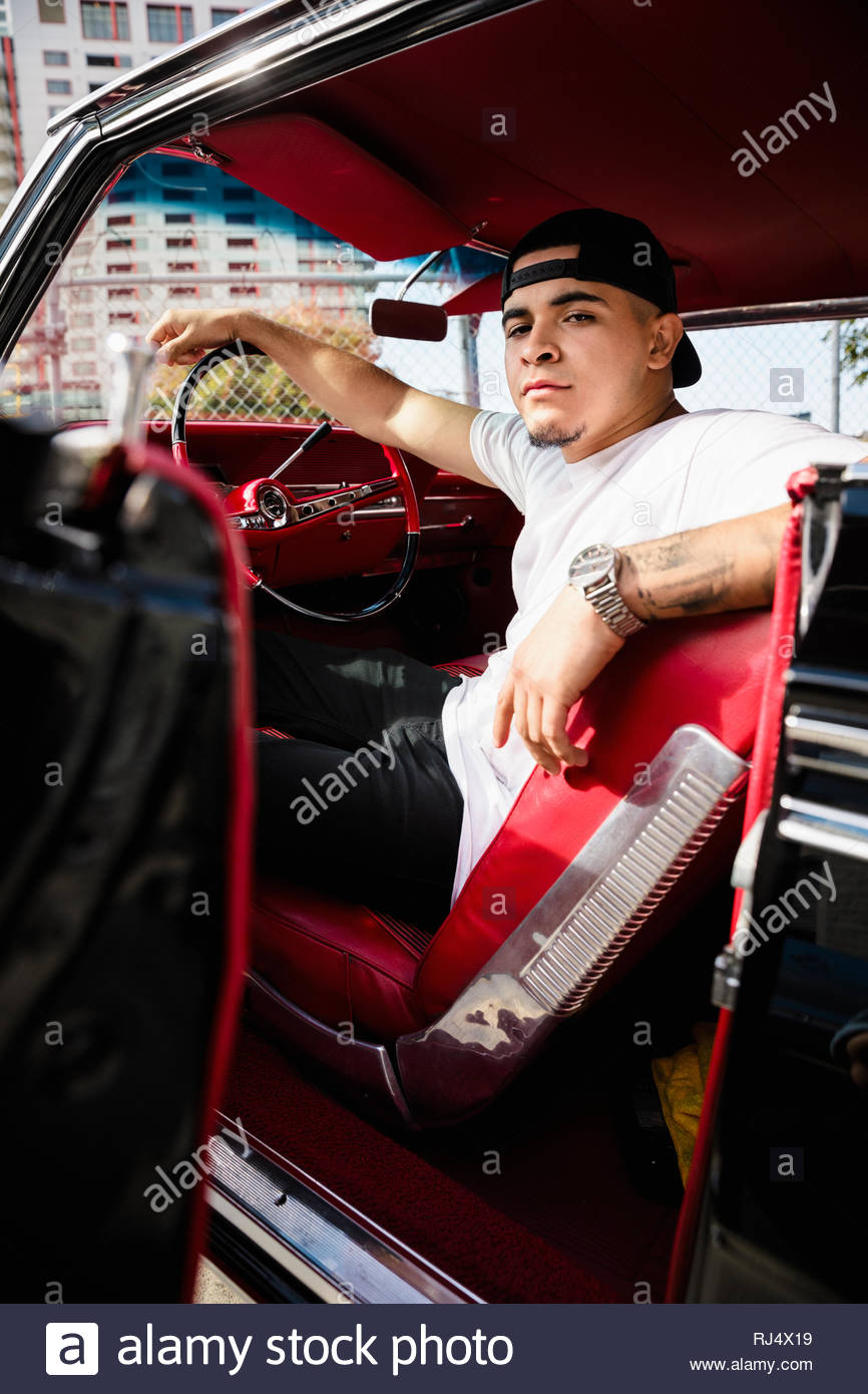 Confiant, cool Latinx Portrait young man in low rider vintage car Photo Stock