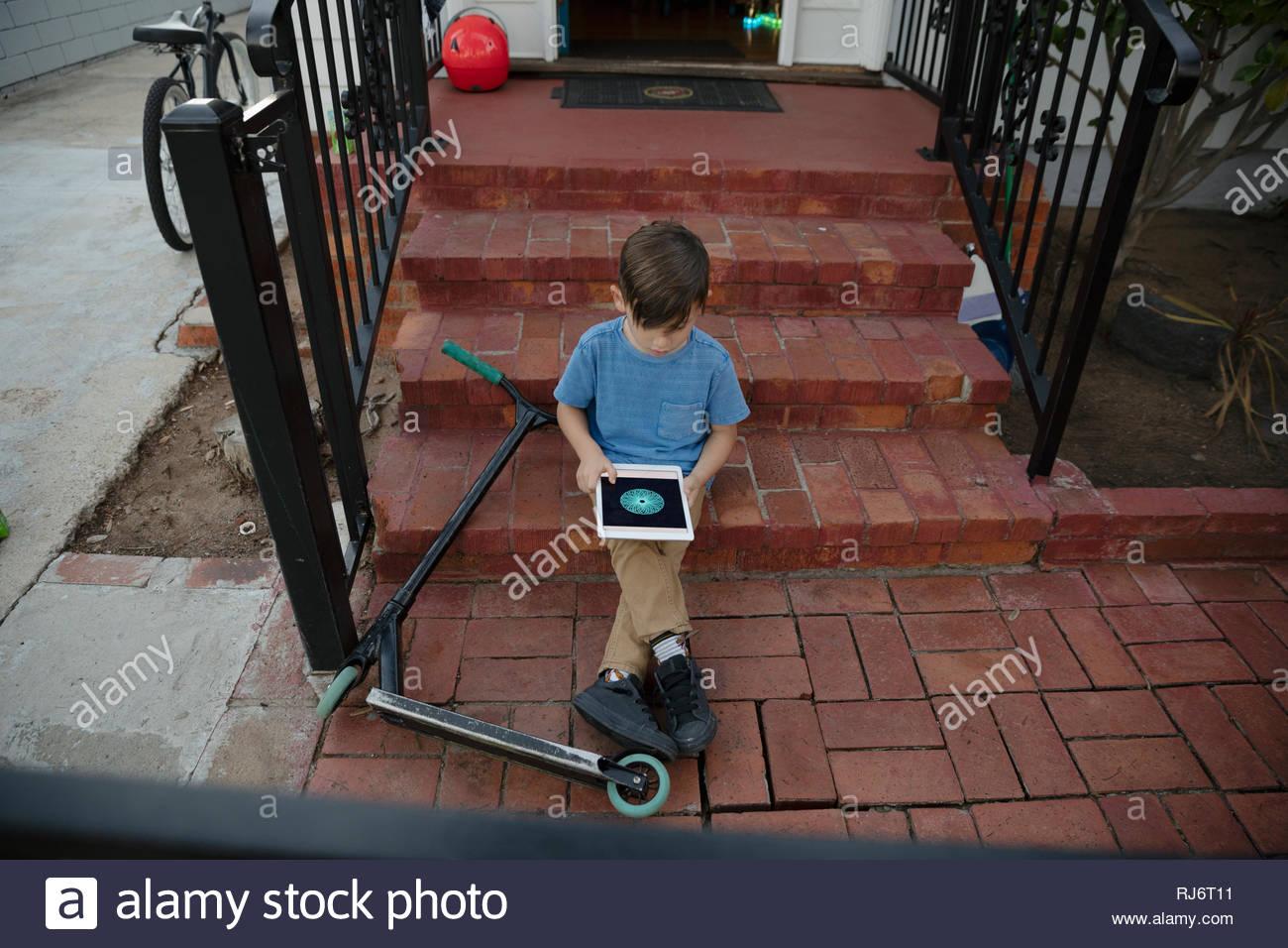 Garçon Latinx avec scooter using digital tablet sur avant stoop Photo Stock