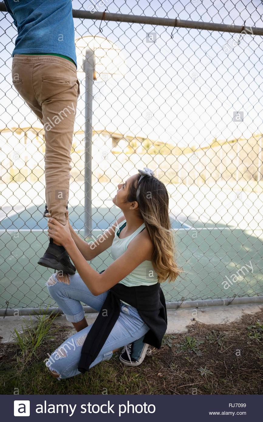 Jeune femme Latinx levée l'homme sur la clôture à court de tennis Photo Stock