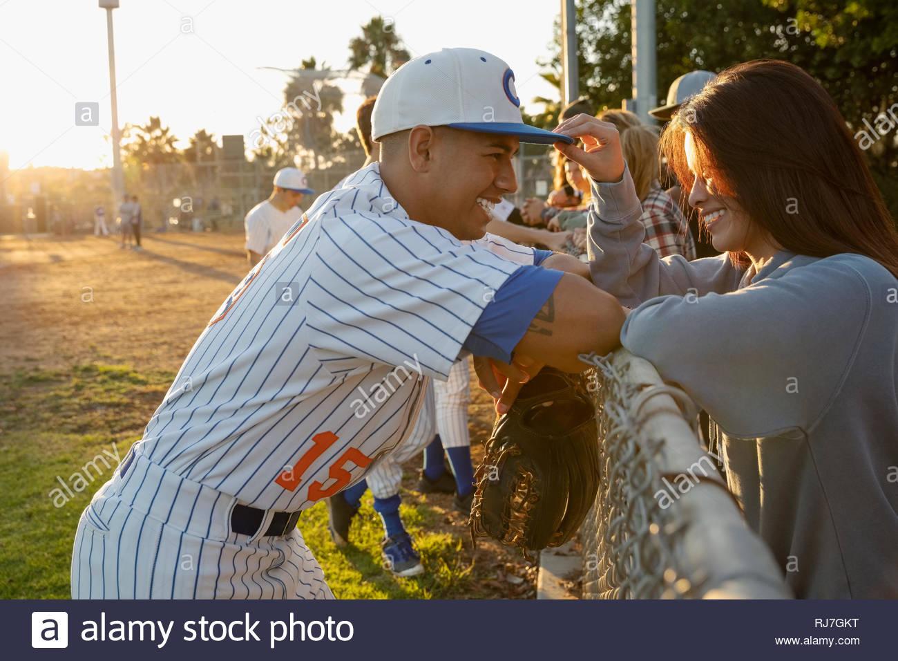Joueur de baseball Latinx heureux de parler avec ma copine à fence Photo Stock