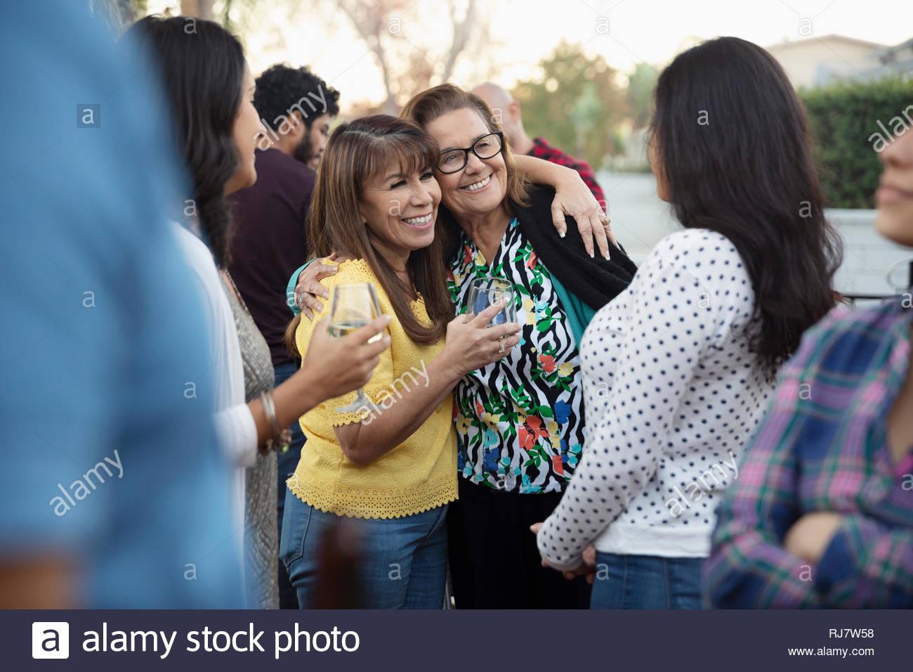 Les femmes Latinx boire du vin et étreindre on patio Photo Stock