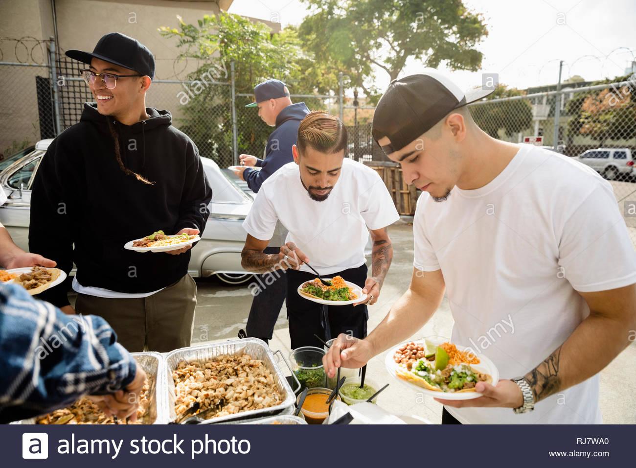 Les hommes Latinx friends enjoying taco déjeuner Photo Stock