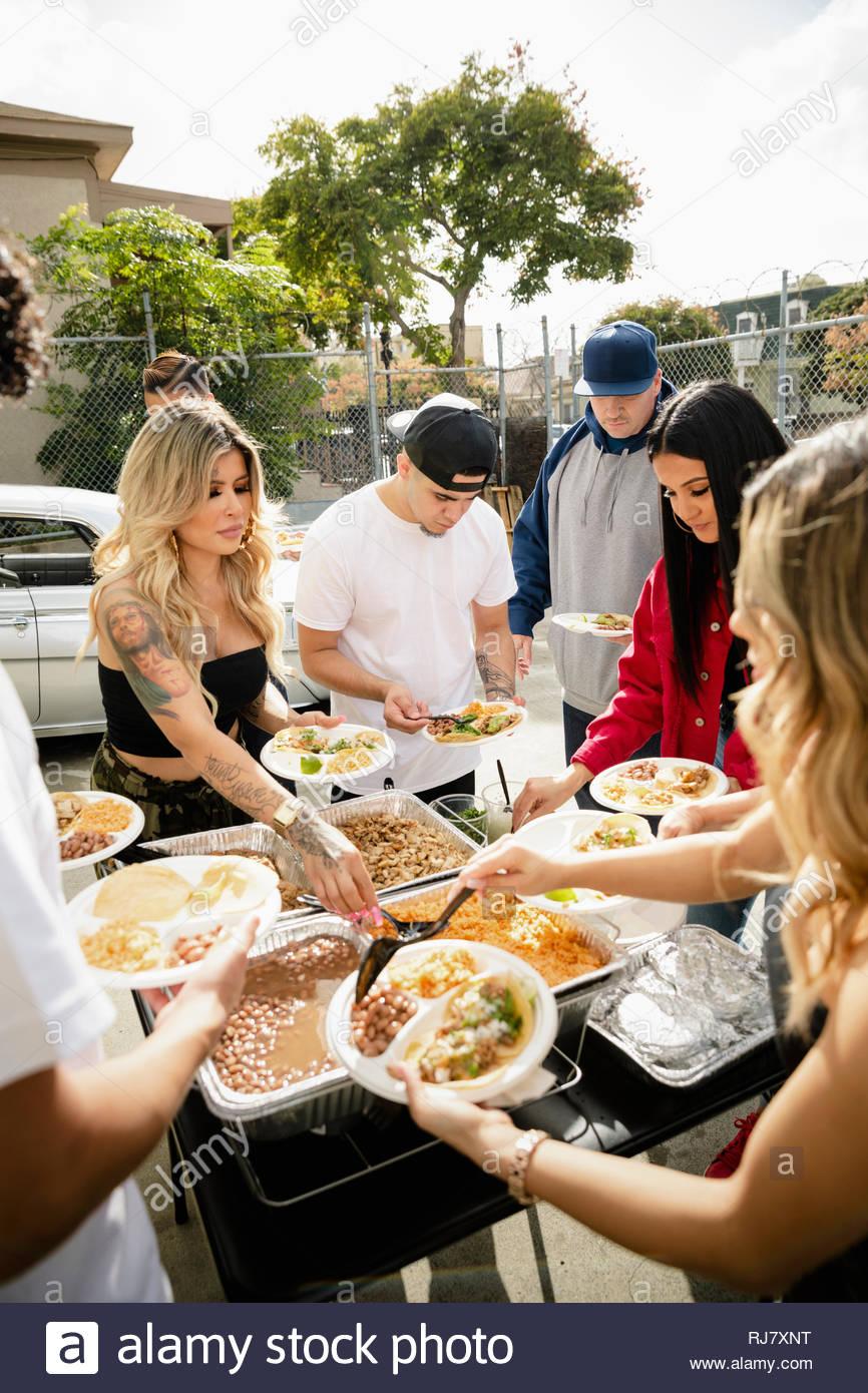 Latinx friends enjoying taco déjeuner au parc de stationnement Photo Stock