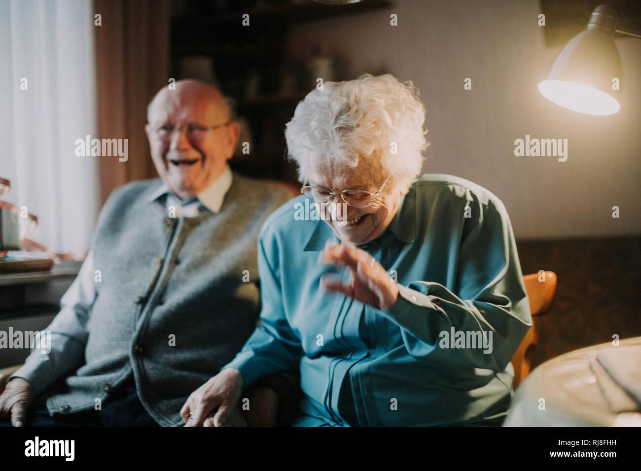 Seniorenpaar lachend sitzt im Wohnzimmer Photo Stock