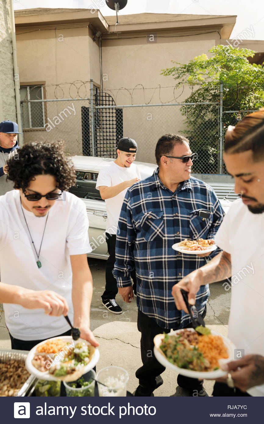 Les hommes Latinx friends enjoying taco déjeuner dans l'entrée Photo Stock
