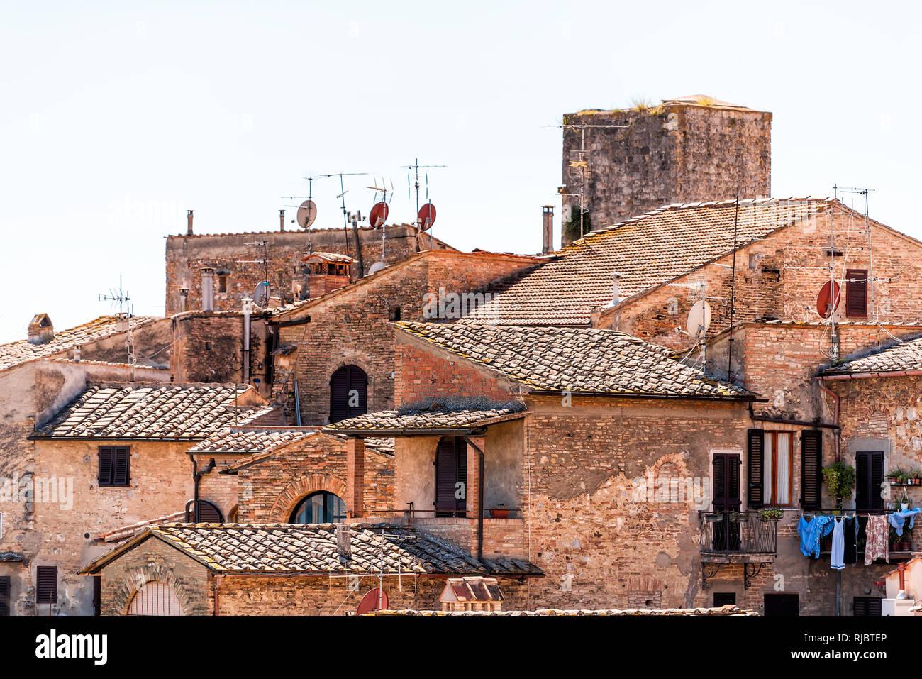 San Gimignano, Italie sur le toit avec la vieille ville historique de bâtiments médiévaux de la ville d'orange en été village en pierre tuiles libre et paraboles capitales Banque D'Images