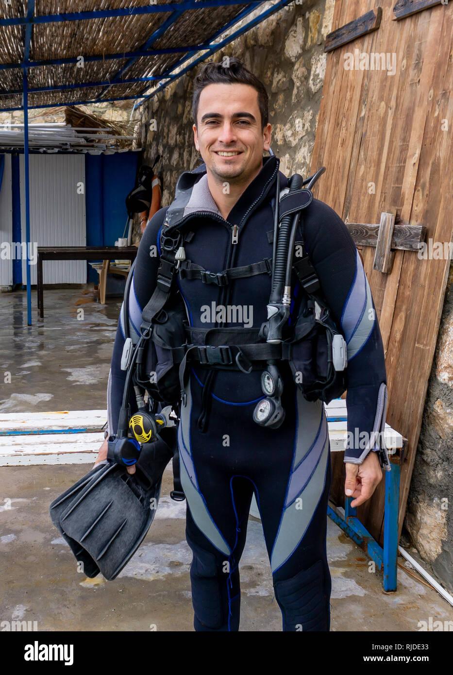 Portrait d'un jeune homme séduisant diver prêt à faire de la plongée avec de l'eau froide combinaison, palmes, gilet stabilisateur, détendeur, source d'air de secours Photo Stock