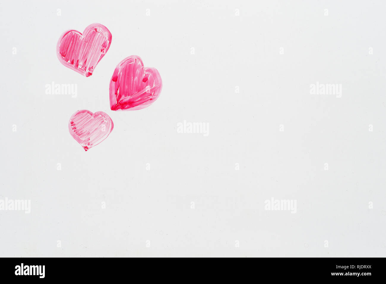 Hand drawn pink Valentines Day hearts sur le coin d'un tableau blanc avec copyspace Photo Stock