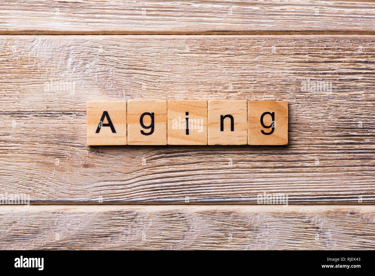 Vieillissement mot écrit sur une cale en bois. Texte sur le vieillissement pour votre table en bois, design concept. Photo Stock