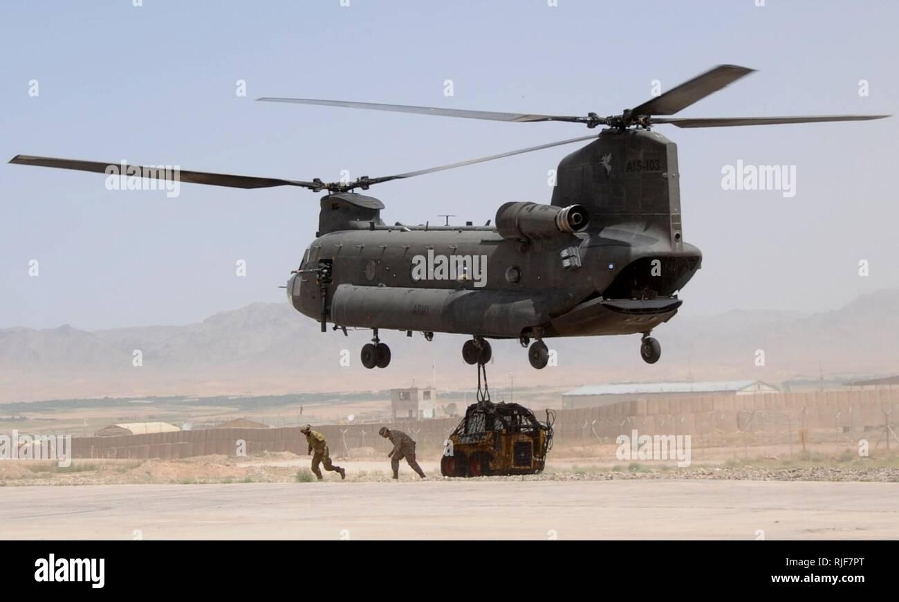 Un U.S. Navy Seabee et un aviateur australien australien s'éloigner d'un hélicoptère CH-47 Chinook de l'armée après avoir fixé un chargement de fret sur la ligne de vol à Force-Southeast d'opérations spéciales du Camp Ripley, Tarin Kowt, la province d'Uruzgan, Afghanistan, le 17 mai. L'équipement est transporté à un site plate-forme de stabilité du Village d'appuyer les projets de construction. Photo Stock