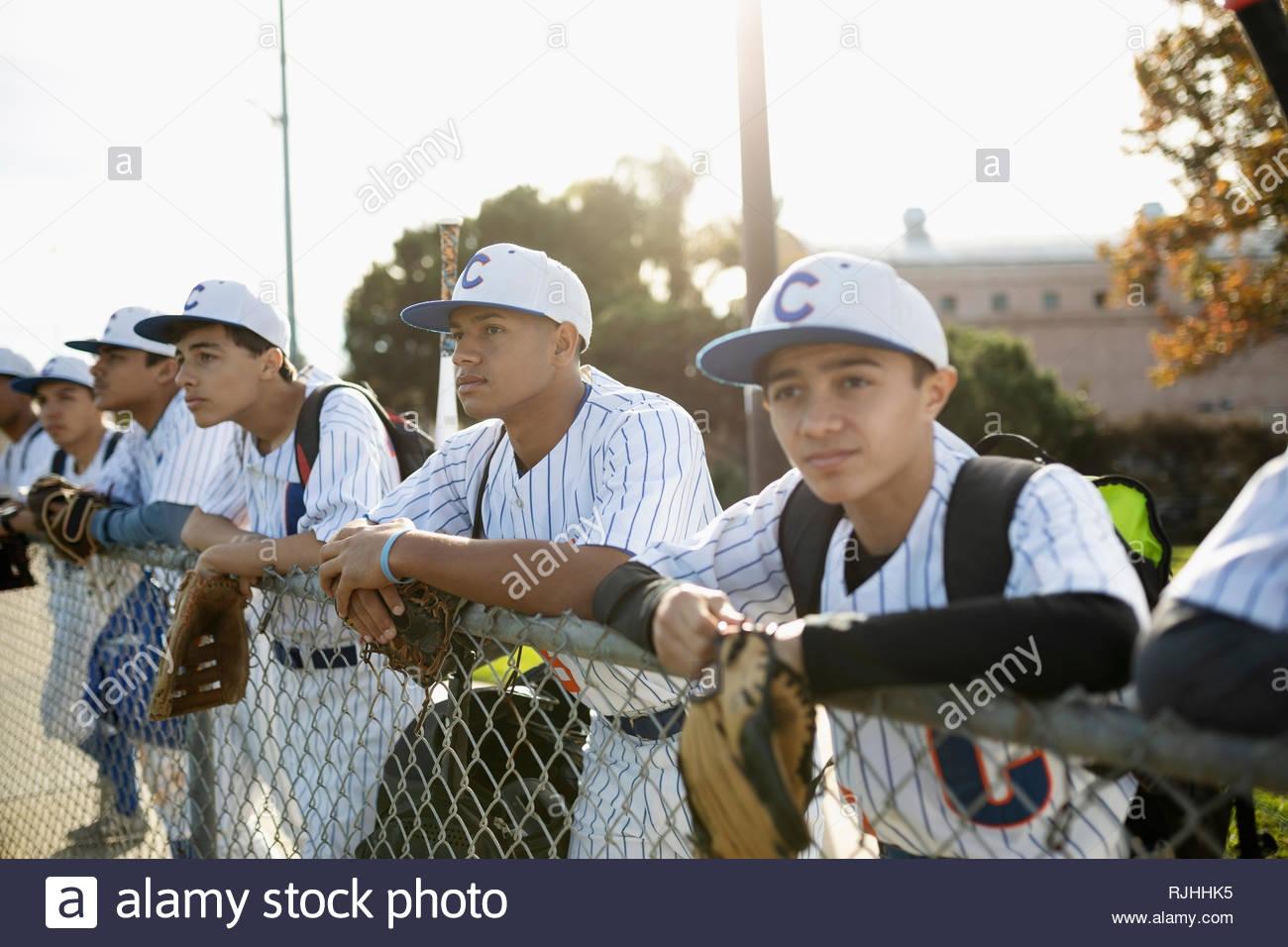 Les joueurs de baseball leaning on fence ensoleillée Photo Stock